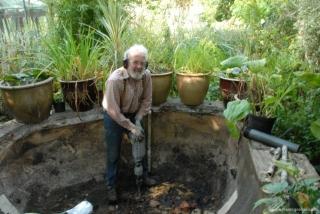 Breaking the concrete pond bottom.